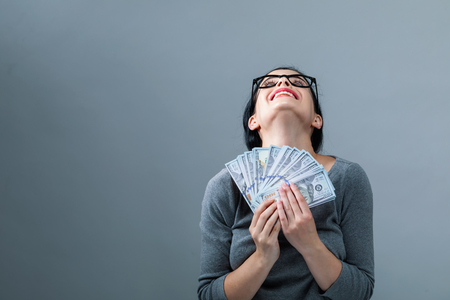 Young woman with a stack of cash USD on a gray background
