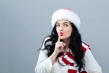 Young woman with Santa hat making a quiet gesture on a gray background