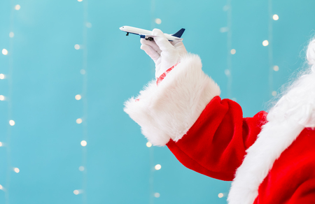 Santa holding a toy airplane on a shiny light blue background Stock Photo
