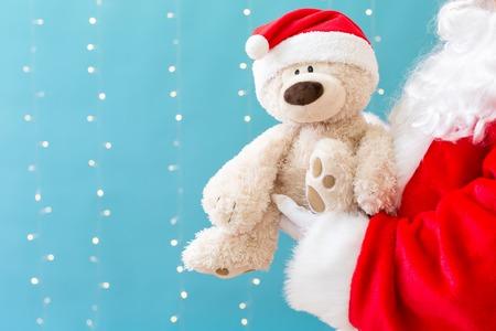 Santa holding a teddy bear on a shiny light blue background Stock Photo