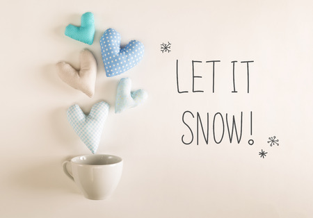 Let It Snow message with blue heart cushions coming out of a coffee cup