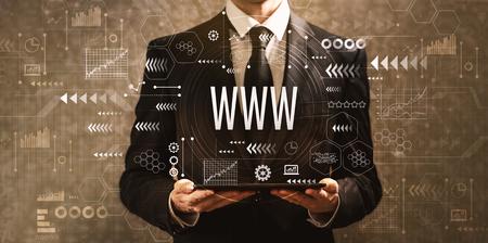 www z biznesmenem trzymającym komputer typu tablet na ciemnym tle vintage