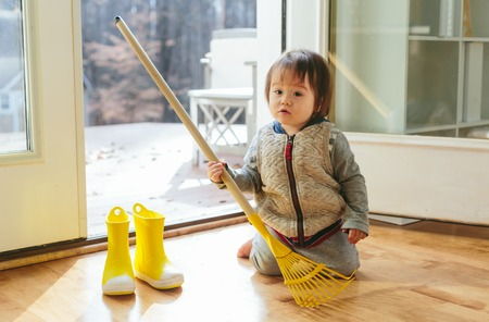 Toddler boy playing with with a rake and boots in autumn
