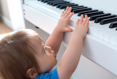 Toddler boy excited to reach up and play the piano Stockfoto
