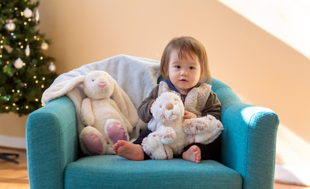 Toddler boy playing with stuffed animals in his house around Christmas time