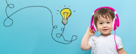 Light bulb with string with toddler boy with headphones on a blue background
