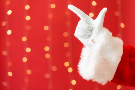 Santa with pointing gesture on a shiny light red background