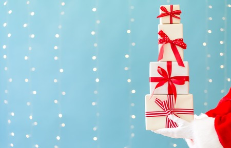 Santa holding Christmas gift boxes on a shiny light blue background