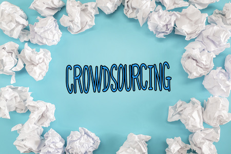 Crowdsourcing text with crumpled paper balls on a blue background