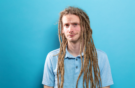 Portrait of a young man with dreadlocks standing against a solid background