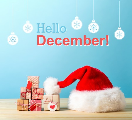 Hello December message with a Santa hat and tiny Christmas gift boxes