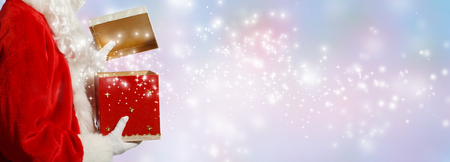 Santa opening a gift box on a shiny light background Stok Fotoğraf