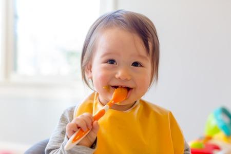 Garçon heureux d'enfant en bas âge souriant tout en mangeant un repas Banque d'images