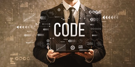 Code with businessman holding a tablet computer on a dark vintage background