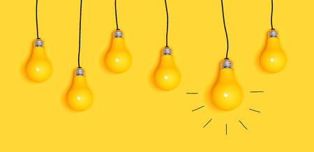 Many hanging light bulbs on a yellow background