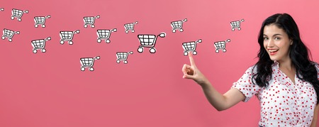 Online shopping with young woman on a pink background