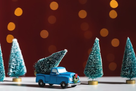 Toy truck carrying a Christmas tree on a shiny light dark red background
