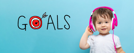 Goals with target with toddler boy with headphones on a blue background Stock Photo