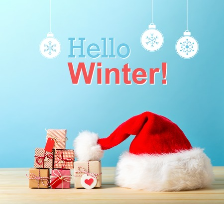Hello winter message with a Santa hat and tiny Christmas gift boxes Reklamní fotografie
