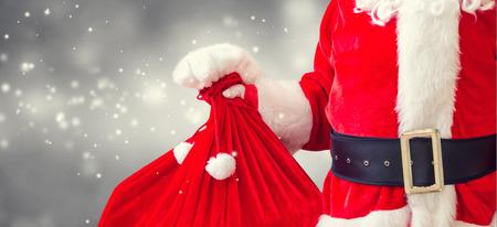 Santa holding a red sack on a shiny light background Stock Photo