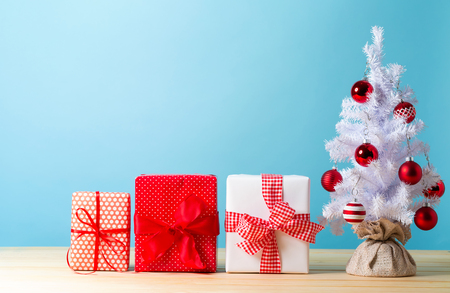 Small white christmas tree with presents on a blue background
