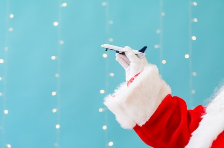 Santa holding a toy airplane on a shiny light blue background Imagens