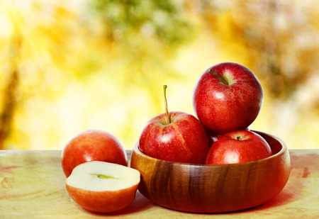Fresh red apples with an autumn sky and foliage background Stock Photo
