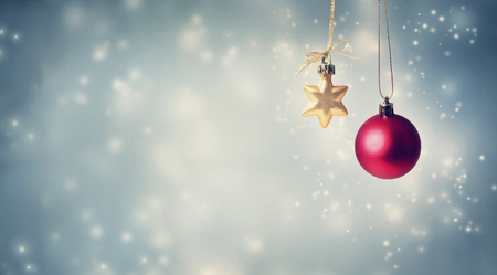 Christmas star and bauble ornaments on a shiny light background