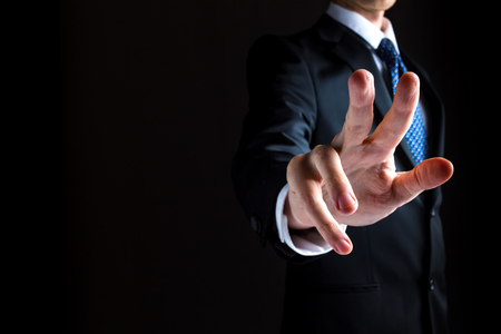 Man in a suit pointing or pressing something on black background