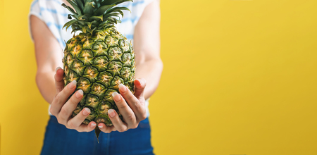 Young woman holding a pineapple on a yellow background Standard-Bild
