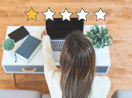 One star rating with woman using her laptop computer Stock Photo