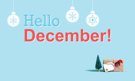 Hello December message with a Christmas gift box and toy tree