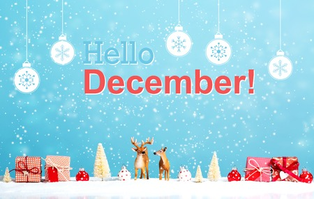 Hello December message with reindeer and Christmas gifts in snowy day