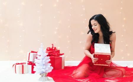 Giovane donna che tiene una confezione regalo su uno sfondo luminoso brillante Archivio Fotografico