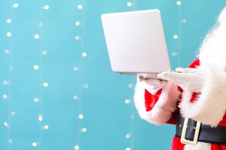 Santa using a laptop on a shiny light blue background