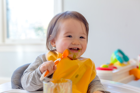 Happy toddler boy smiling while eating a meal