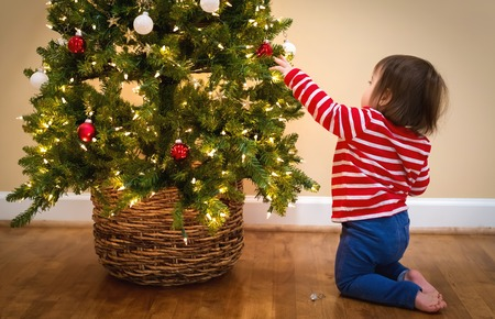 Toddler boy decorating the Christmas tree in his house Stock Photo