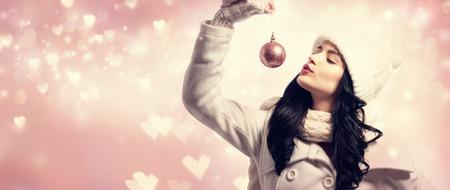 Woman holding Christmas bauble on shiny hearts background Stock Photo