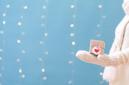 Woman holding a Christmas gift box on a shiny light blue background Stok Fotoğraf