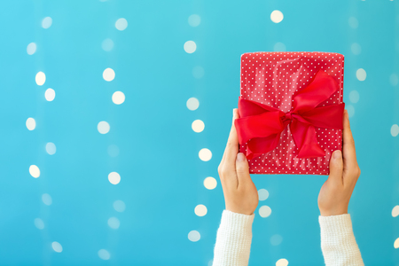 Person holding a Christmas gift box on a shiny light blue background