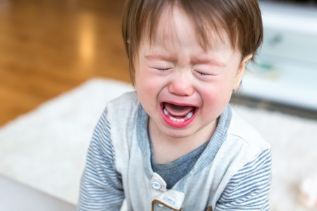 Upset toddler boy screaming and crying in his house