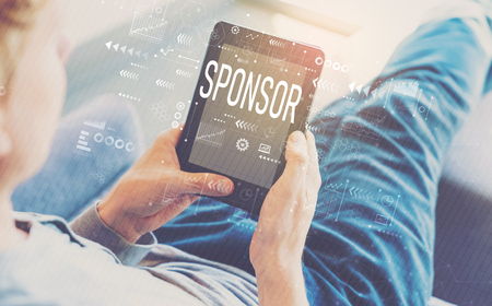 Sponsor with man using a tablet in a chair Stock Photo
