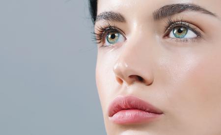 Junge Frau mit Kontaktlinsen auf einem grauen Hintergrund Standard-Bild