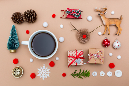 Christmas ornaments with coffee cup on a light brown paper background Banco de Imagens