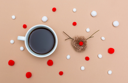 Cup of coffee with Christmas reindeer pompom on a light brown paper background
