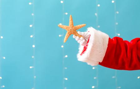 Santa holding a starfish on a shiny light blue background