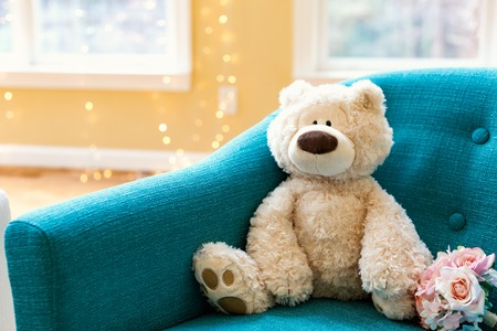 Teddy bear and a flower bouquet on a chair in a room