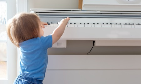 Toddler boy excited to reach up and play the piano Imagens