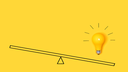 Idea light bulb on a scale on a yellow background