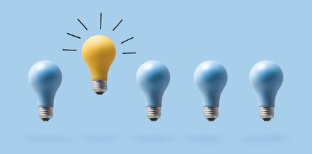Un concepto de idea excepcional con bombillas de luz sobre un fondo azul. Foto de archivo